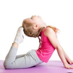 Kid doing fitness exercises on mat. Isolated on white background.
